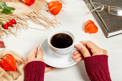 A woman holding a Cup of coffee on the table is a book and glasses. The concept of rest in the autumn season