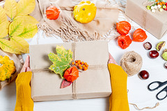 Beautifully packaged gift in autumn style in women's hands. Family holiday concept, Thanksgiving Day