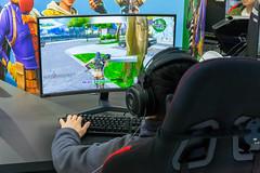 Kind spielt das Computerspiel Fortnite auf einem Nvidia Curved-Monitore