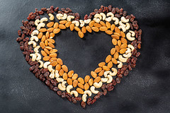 Heart lined from cashew nuts, almonds and raisins on a black background. Top view