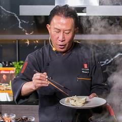 Koch füllt frische Krabbenchips mit Essstäbchen auf einen weißen Teller