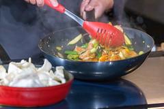 Koch kocht eine asiatische Gemüsepfanne mit Garnelen und Krabbenchips