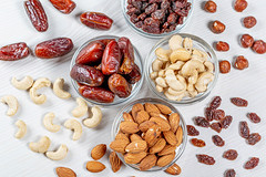 Nuts and dried fruits on a white wooden background. The concept of healthy food