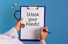 Doctor holding clipboard with Wash your hands text