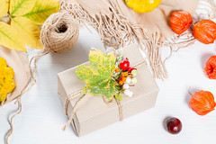 Packaged gift with yellow leaves, berries, scarf and thread on white wooden table. Family holiday concept, Thanksgiving Day