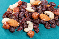 Raisins and different nuts on a green background
