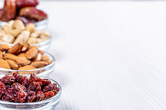 Glass bowls with nuts and dried fruits on white wooden background with free space