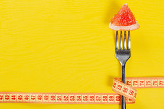A piece of ripe grapefruit on a fork wrapped with measuring tape on a yellow background as a symbol of weight loss