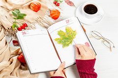 Woman puts maple leaf in empty notebook on autumn background of white table with scarf, coffee Cup and glasses