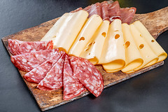 Sliced salami, ham, jerky and cheese on an old wooden kitchen Board