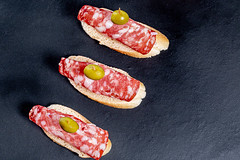 Baguette sandwiches with salami and olives on a black background. Top view