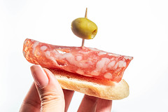Sandwich with salami and green olive in a woman's hand on a white background