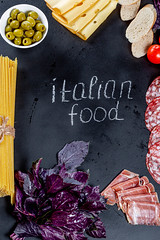 """The inscription """"Italian food"""" on a black background with a frame of products of Italian cuisine"""