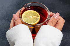 Close-up of a Cup of black tea with a piece of lemon in women's hands