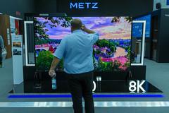 Mann steht vor dem Metz 120 Zoll 8K LCD-Fernseher mit 3m Bildschirmdiagonale