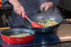 Preparing asian food during cooking show with live audience