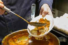 Geschnittene Currywurst wird mit Currysauce übergoßen