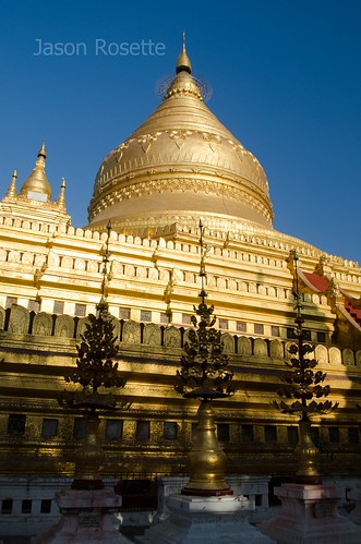 Golden temple in Bagan, Myanmar, with metal spires in foreground (Vertical #2)