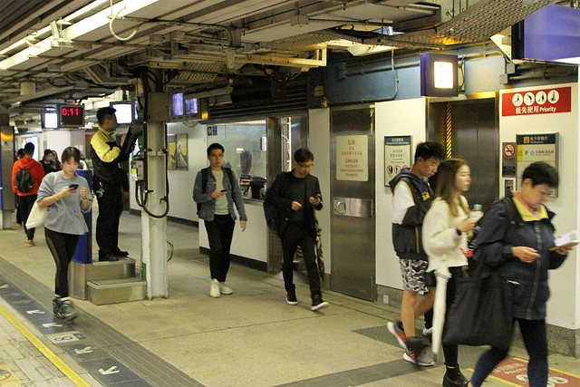 Platform staff give the all clear for a train to depart Tai Wai station