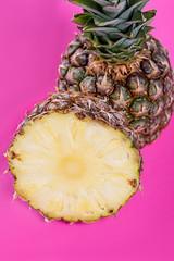 Fresh ripe pineapple halves on pink background