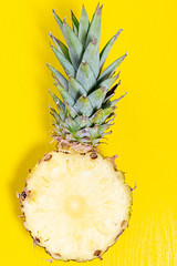 Half ripe pineapple with green leaves on a yellow background