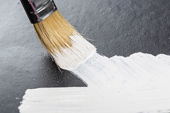 Draws a brush with white paint on a black background close-up
