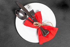 Fork, knife and spoon with red napkin and white plate on black background. Top view
