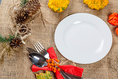 Empty plate with Cutlery on burlap with autumn background