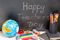 Globe and school supplies with teg Happy Teacher's Day on blackboard