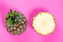 Two halves of a ripe pineapple on a pink background