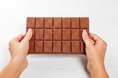 Large milk chocolate in women's hands
