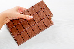 Eaten large milk chocolate in a woman's hand