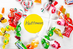 Colorful lollipops and candies on white background with Halloween tag. Top view