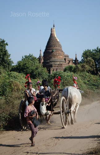 Kids play on departing wagon with small temple nearby, Bagan, Myanmar