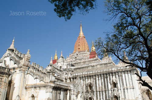 White temple with golden peak seen with tree canopy in Bagan, Myanmar (horizontal)