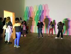 "Image by esallen52 (183909356@N03) and image name Your Uncertain Shadow photo  about 'Your Uncertain Shadow' is an artwork in the exhibition ""In Real Life"" by Olafur Eliasson at Tate Modern. It has five coloured spotlights arranged in a row on the floor, directed at a white wall. Visitors' shadows are projected as they move around the room, varying in size and colour inten"