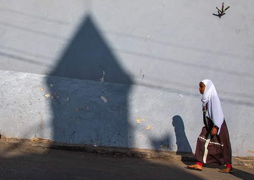 Ethiopian woman passing in front of the shadow of a mosque minaret in the street, Harari region, Harar, Ethiopia