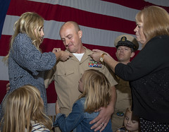 Chief Hospital Corpsman Richard Utley is pinned by his wife and his mother during a ceremony.