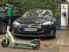Elektro-Mobilität in Köln: Mit dem Lime-Scooter zur TankE-Ladestation, um das Model S von Tesla mit RheinEnergie-Strom zu laden