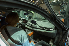 Woman sits inside the limited hybrid car BMW i8 Ultimate Sophisto Edition to look over the interior