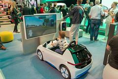 Symbolbild für umweltfreundliche, zukunftsorientierte Autos: kleines Kind spielt ein Fahrsimulationsspiel im Modellauto von VW