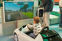 Kleine Fahrschule: Kleinkind im Spielzeugauto von Volkswagen, beim E-Mobilitäts-Fahrsimulator, Videospiel auf der IAA
