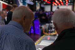 Two elder men looking at the e-tron drivetrain for all-electric vehicles by Audi