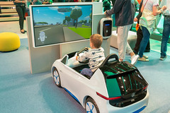 Tiny driving school: Child in a VW toy car, playing a driving simulation game at car exhibition IAA