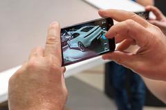 Instagramer auf der Autoaustellung: Mann macht ein Bild mit dem Smartphone vom Elektro-Sportwagen Taycan Turbo S von Porsche