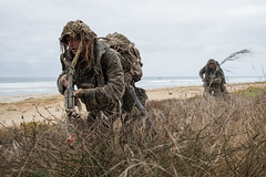 Sailor and Marine change positions while securing a beachhead during a small boat raid.