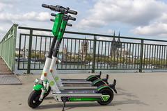 Parkende Lime E-Scooter mit Blick auf Köln