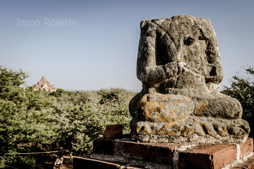 Headless Ganesh or Buddha Statue in Burma with Distant Temple