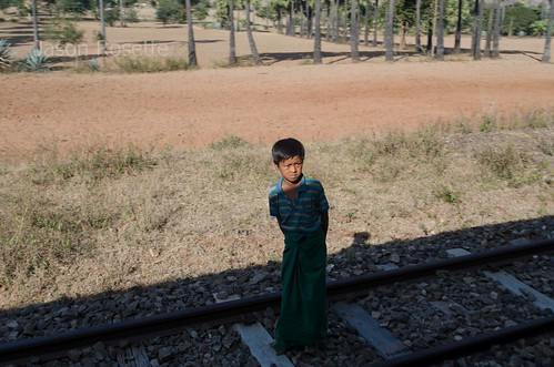 Boy in Burma Warily Looks Up  at Train from Shadows