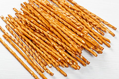Pretzel sticks on white wood background